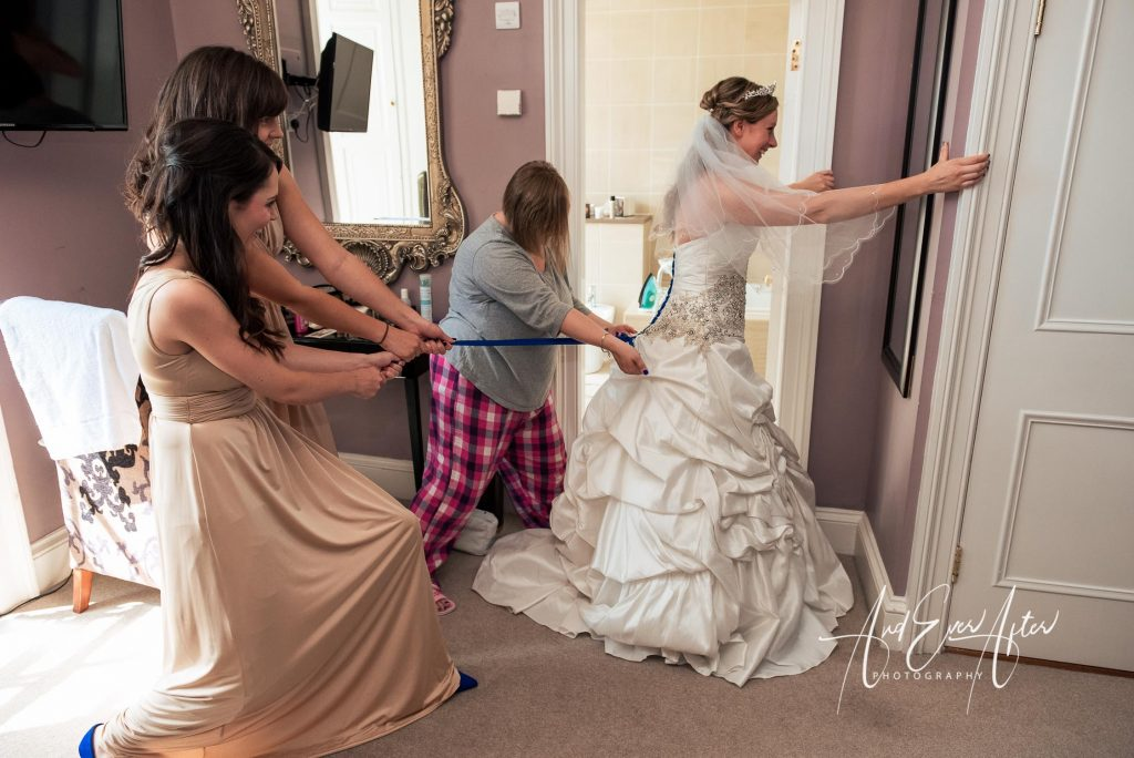bride putting wedding dress on with help from bridesmaids