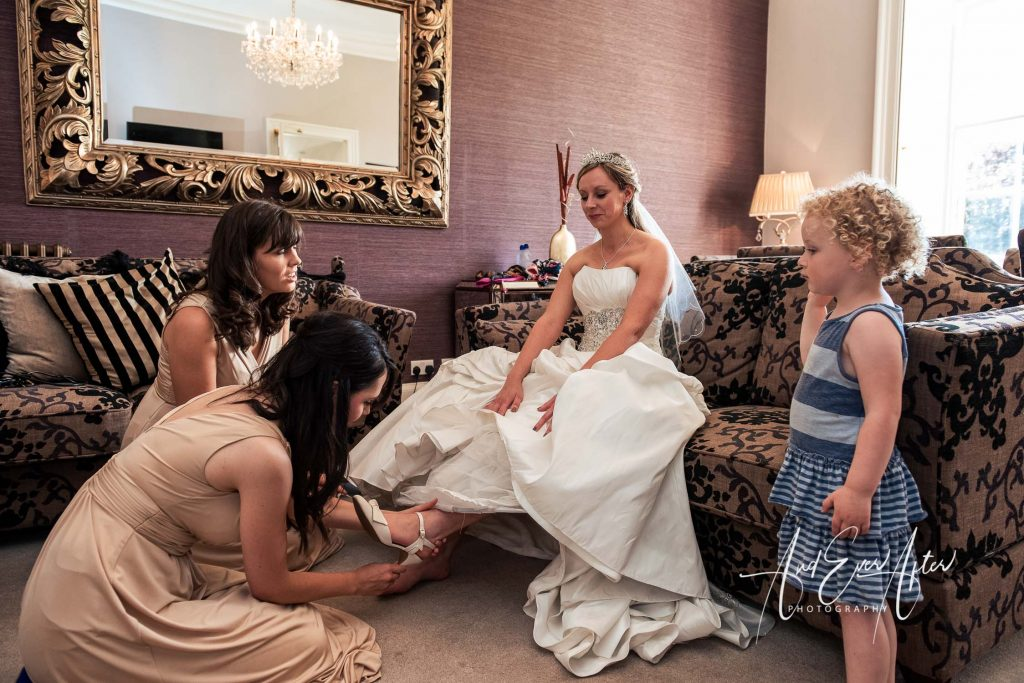 bride being helped with her wedding day shoes