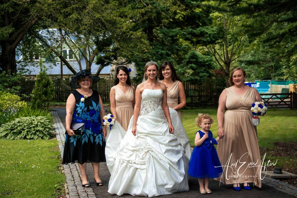 bridal party walking towards the wedding ceremony On their wedding day at Carberry Towers Mansion Hotel