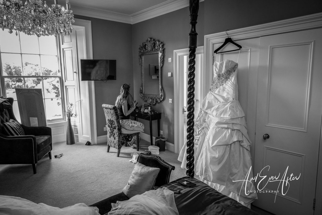 bride getting ready with wedding dress in picture