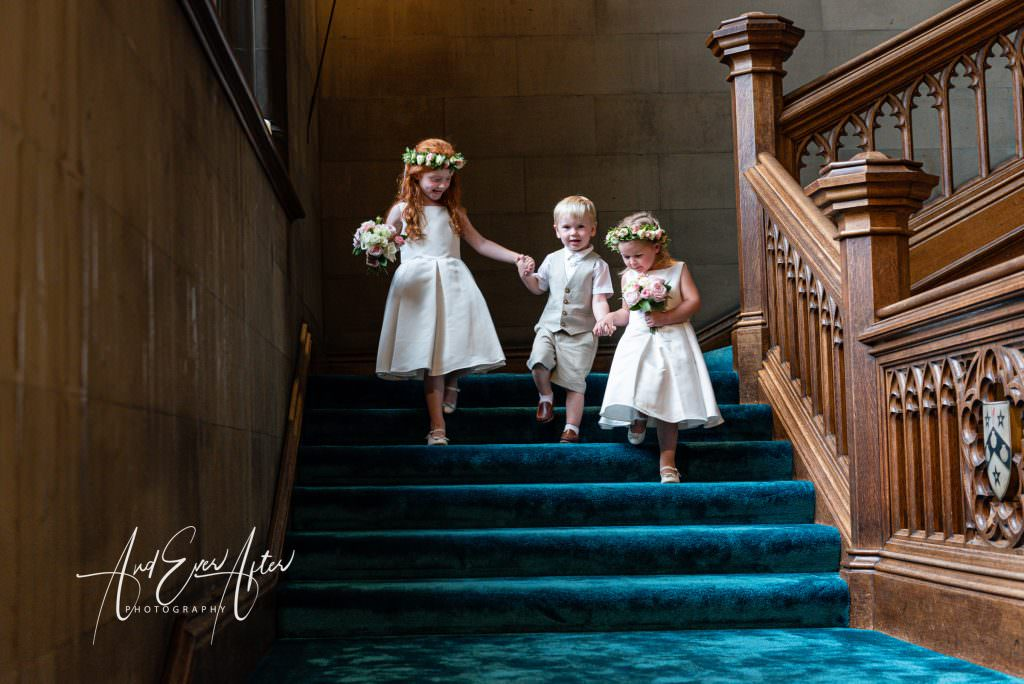 Flower gils and page boys walking down starirs at Maten Hall on wedding day