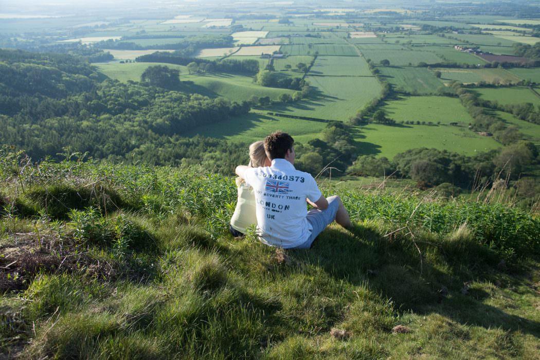 engaged couple, couple sitting on hillside, pre wedding photoshoot