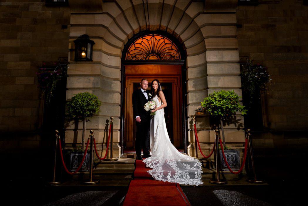 bride and grrom on steps of Crathorne Hall