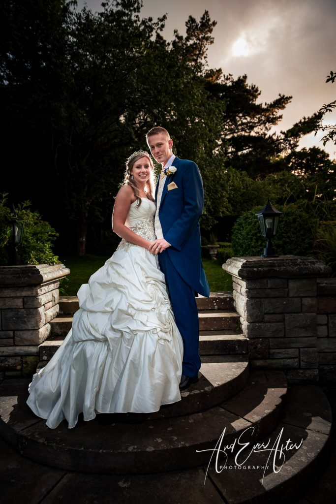 bride and grrom together on their wedding day stood by stone steps