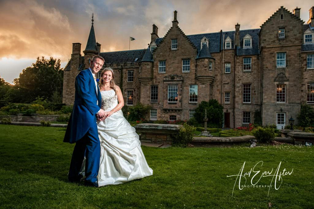 bride and groom stood in front of Carberry Towers Hotel