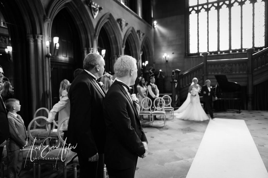 wedding ceremony showing the groom looking back at his bride walking up the aisle at Matfen HAll