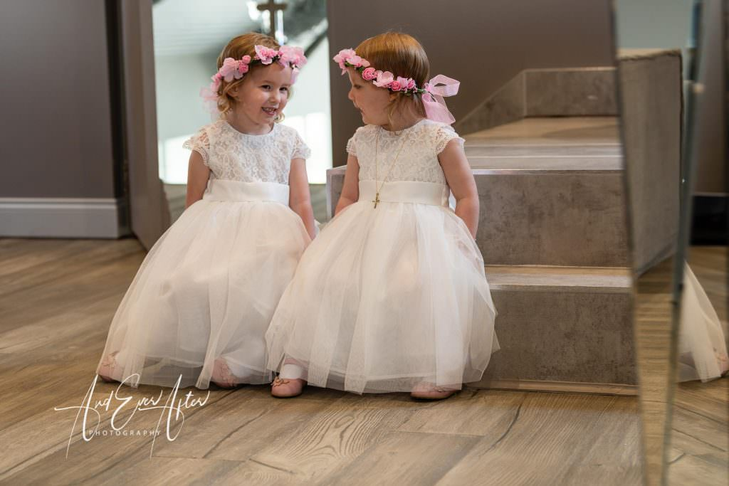 flower girls sitting down getting ready for the big day