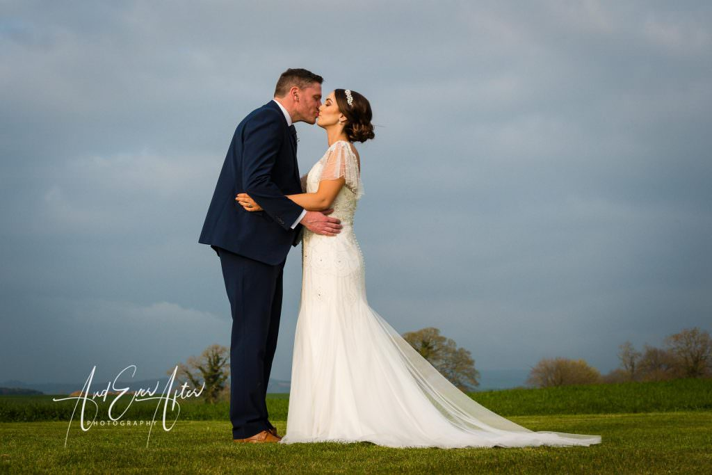 Bride and groom kissing in field at Thief Hall