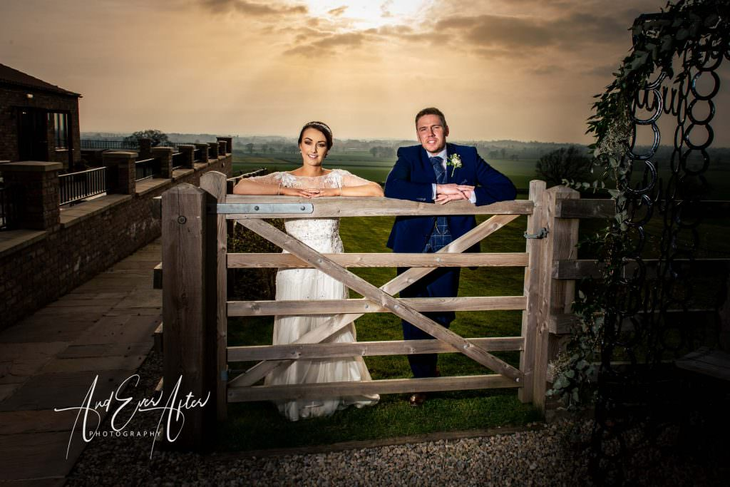 bride and groom stood by gate at Thief Hall