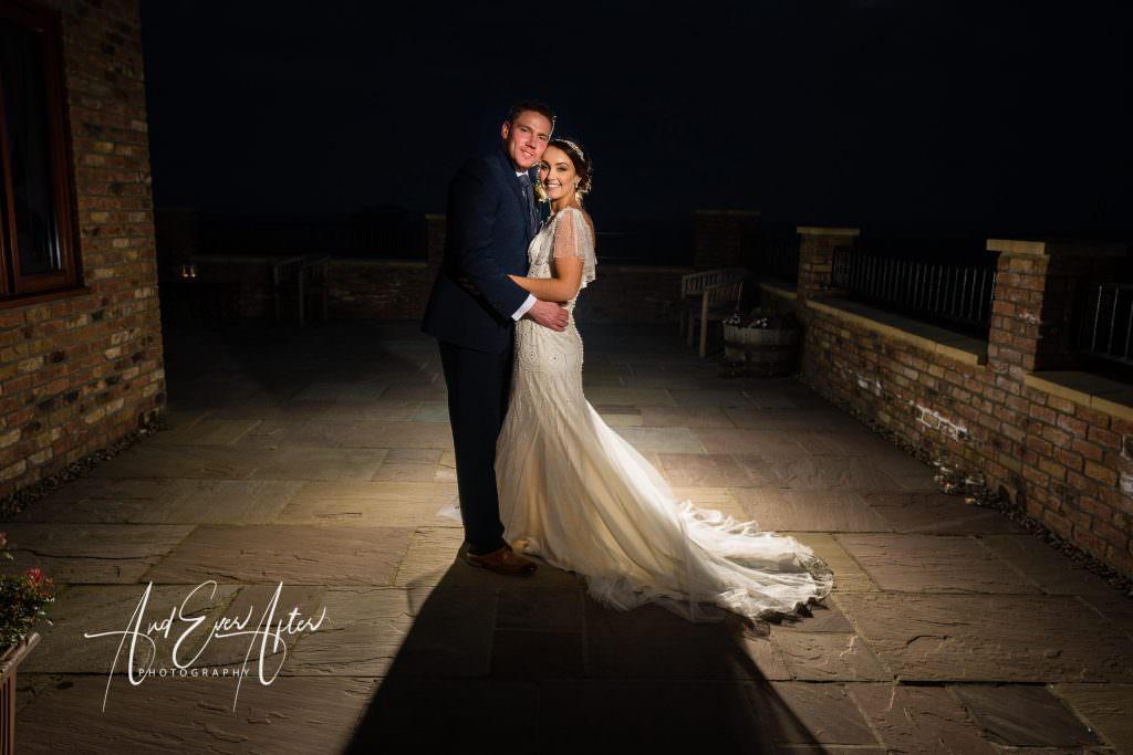 Thief hall wedding photographer bride and groom stood for evening photograph on patio