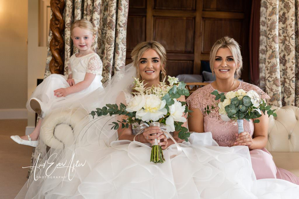 wedding day bridal preparations at Goldsborough Hall, bride , maid of honour and flower girl posing for a photograph