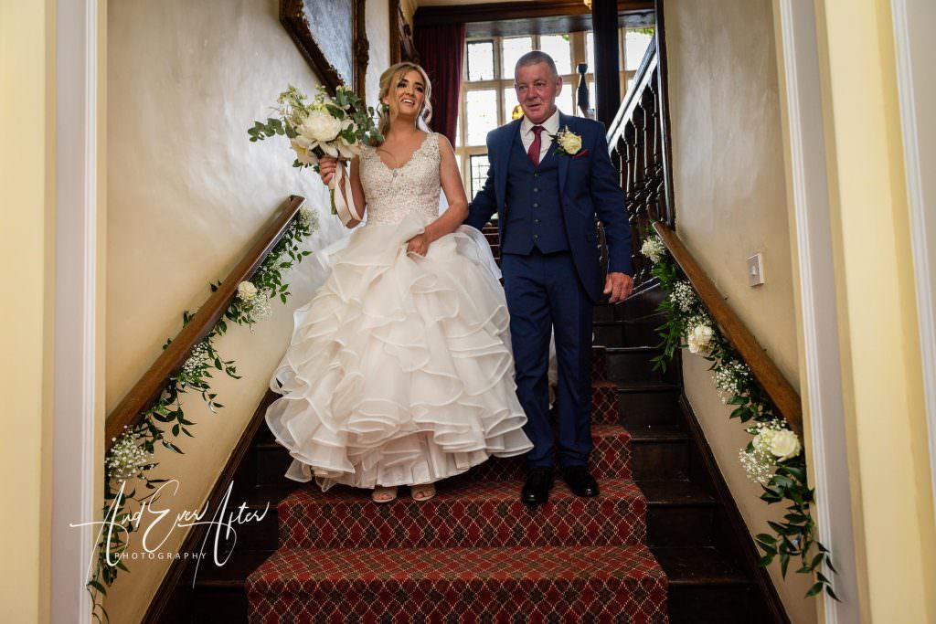 wedding photography at Goldsborough Hall, the bride and her father walking to the church for the wedding ceremony