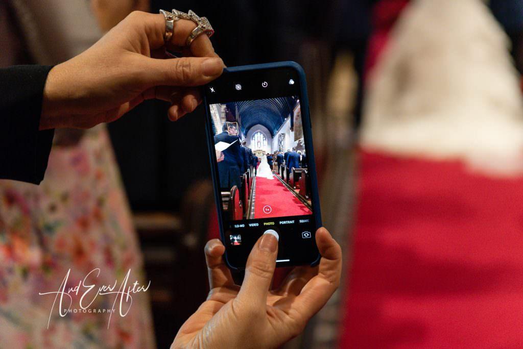 wedding photography at Goldsborough Hall,a wedding guest using their camera phone