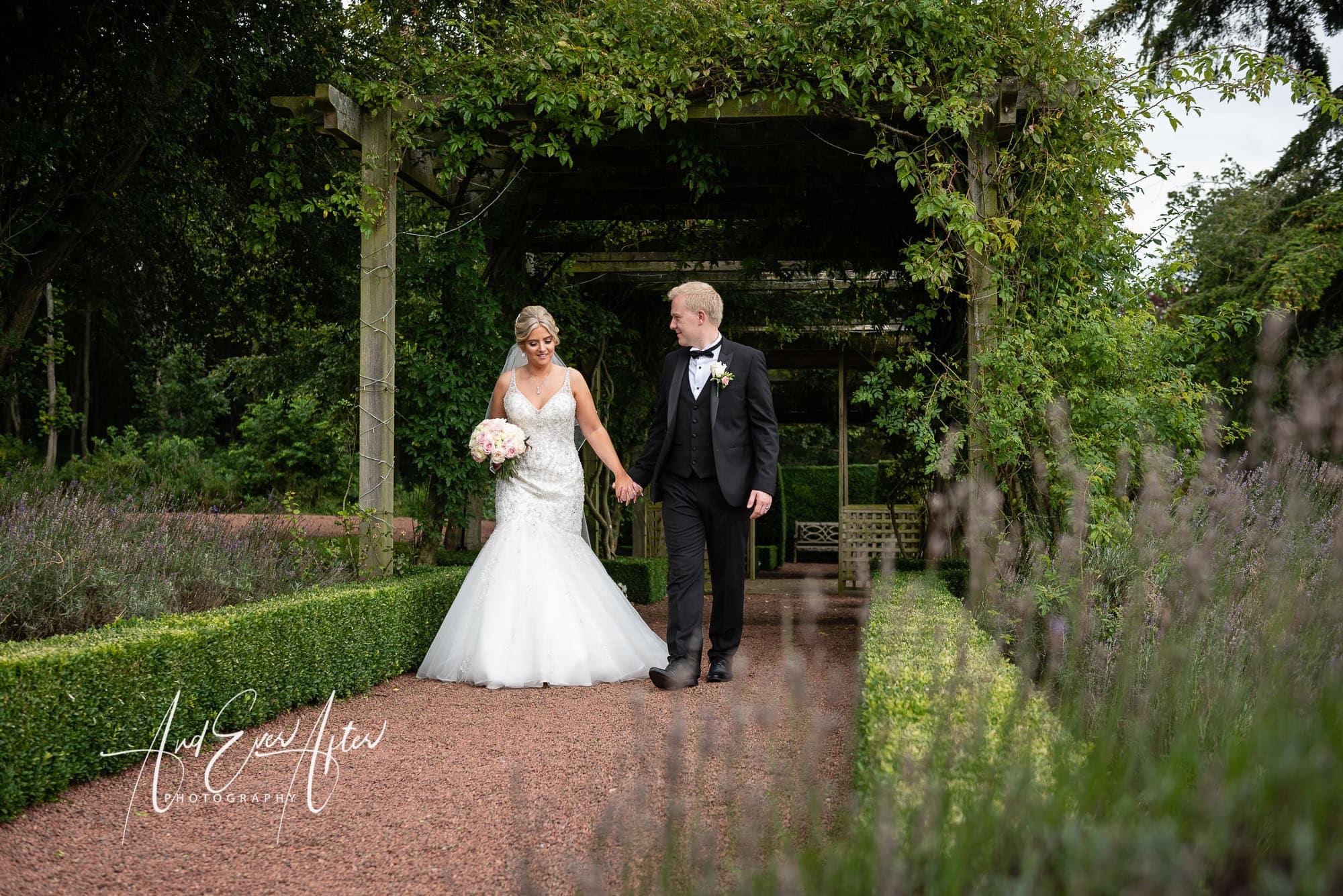 Matfen Hall Wedding Photography, bride and groom walking at Matfen