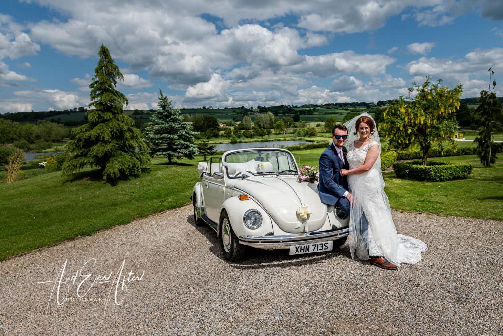 bride and groom sat on wedding car, yorkshire wedding barn