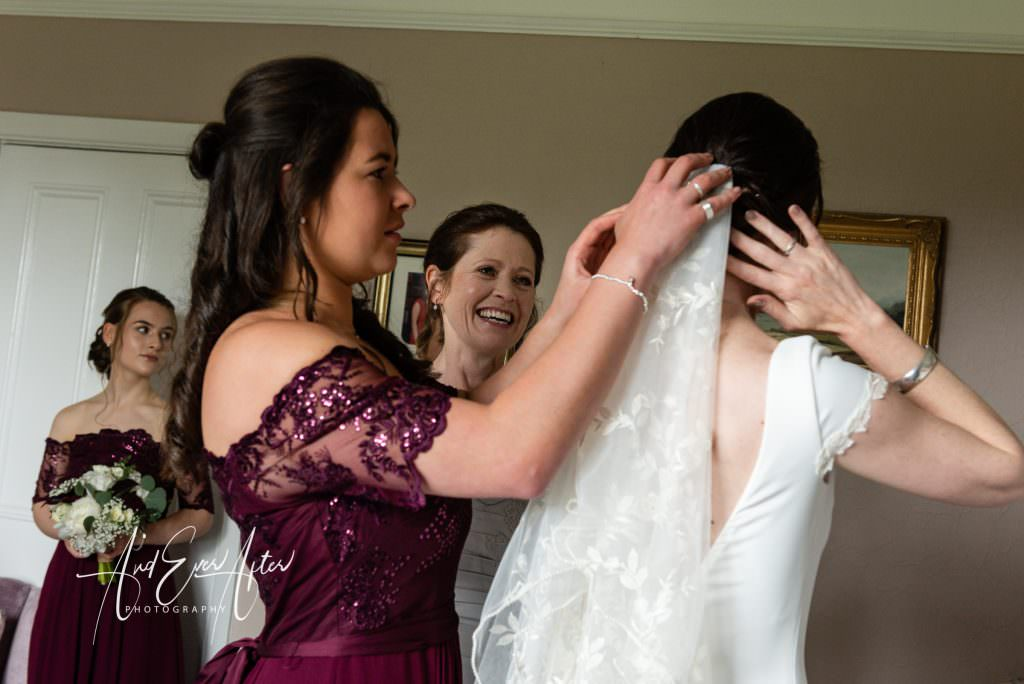 Bride preparing for wedding day with bridesmaid and mother