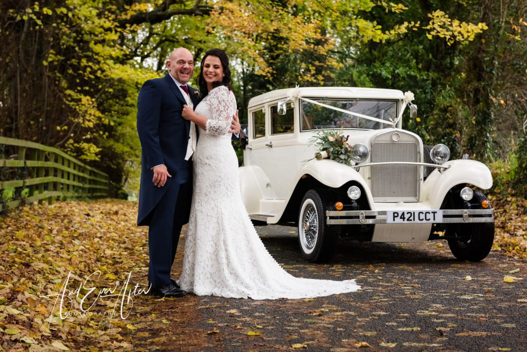 bride and groom stood together in a leafy lane next to their wedding car