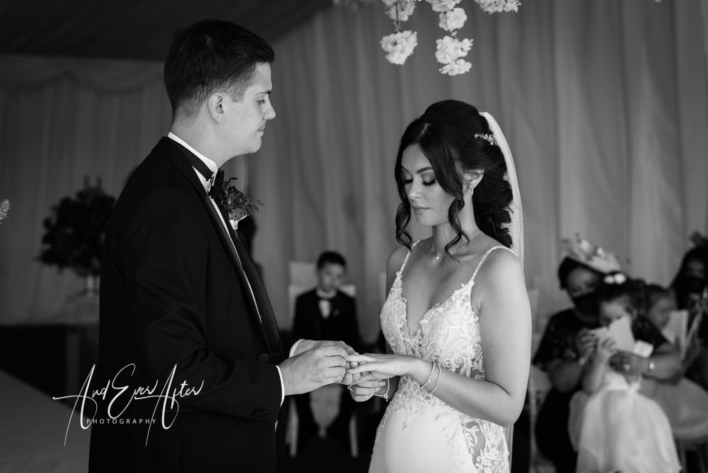 bride and groom during their wedding ceremoiny exchanging rings