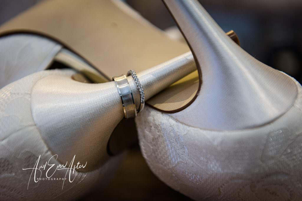 Wedding day shoes displaying wedding rings