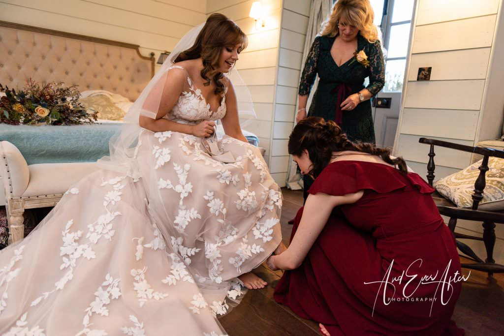Middleton lodge wedding day with bride being helped into her wedding shoes