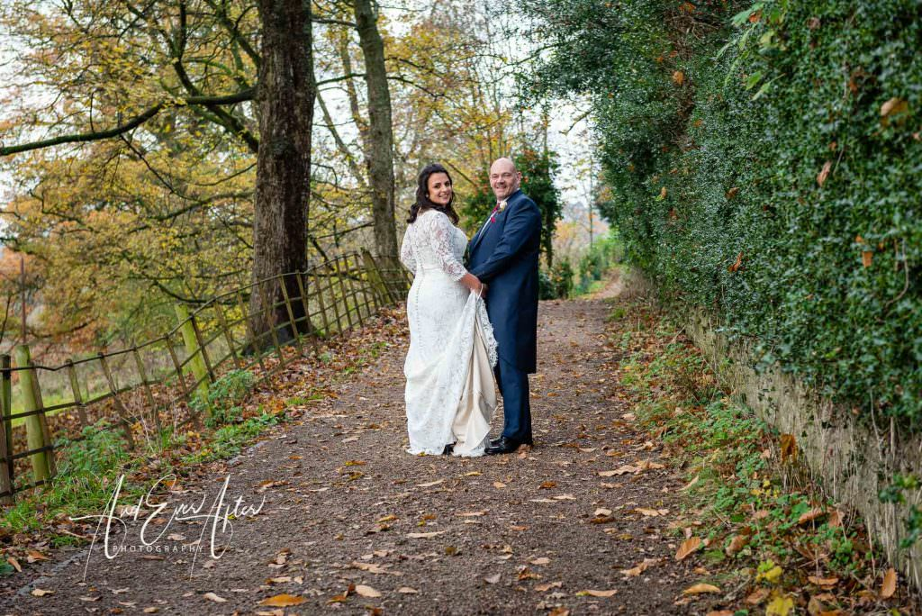 bride and groom being photographed stood at easby abbey in north yorkshire