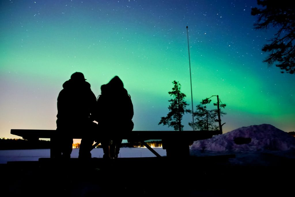 man and woman sat on bench under the northern lights