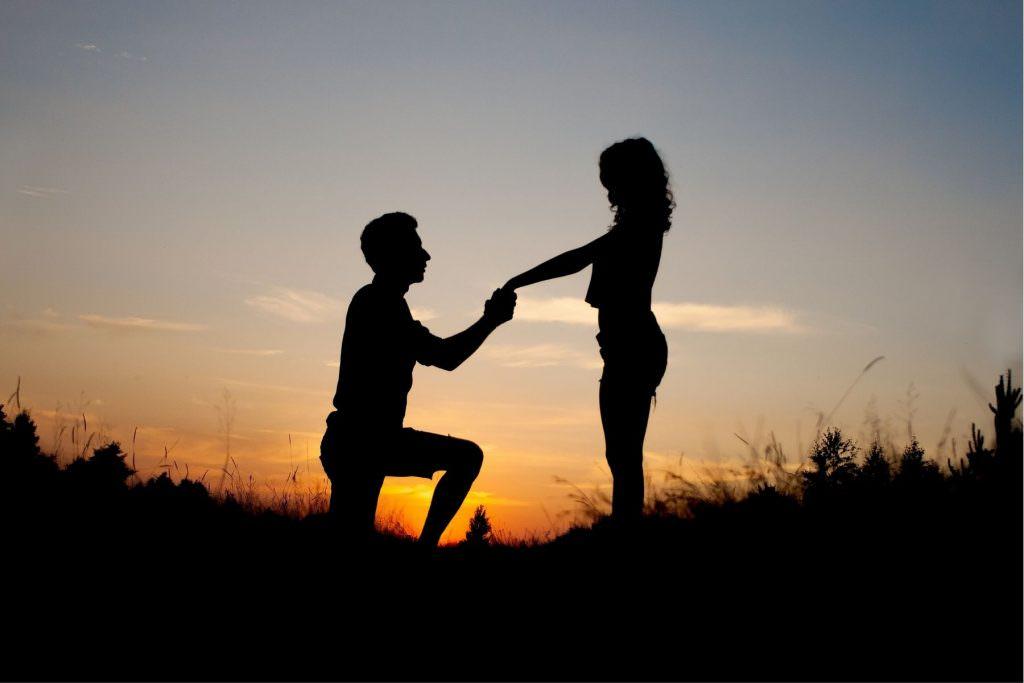 Silohette of amn and woman doing wedding proposal.