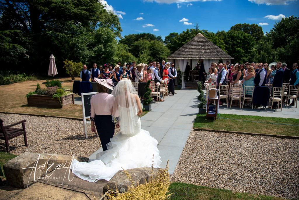 Bride and mum walking doen the aisle at their outdoor wedding ceremony