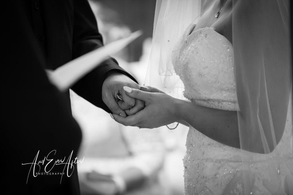bride and groom holding hands at the outdoor wedding ceremony