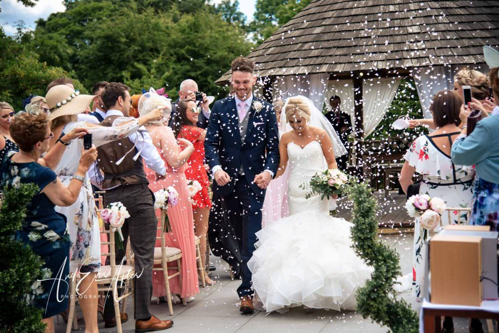 bride and groom walking down the aisle after getting married at the outdoor wedding ceremony