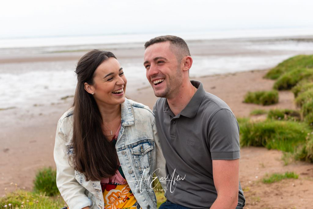pre wedding photoshoot with bride and groom to be cuddling on the beach