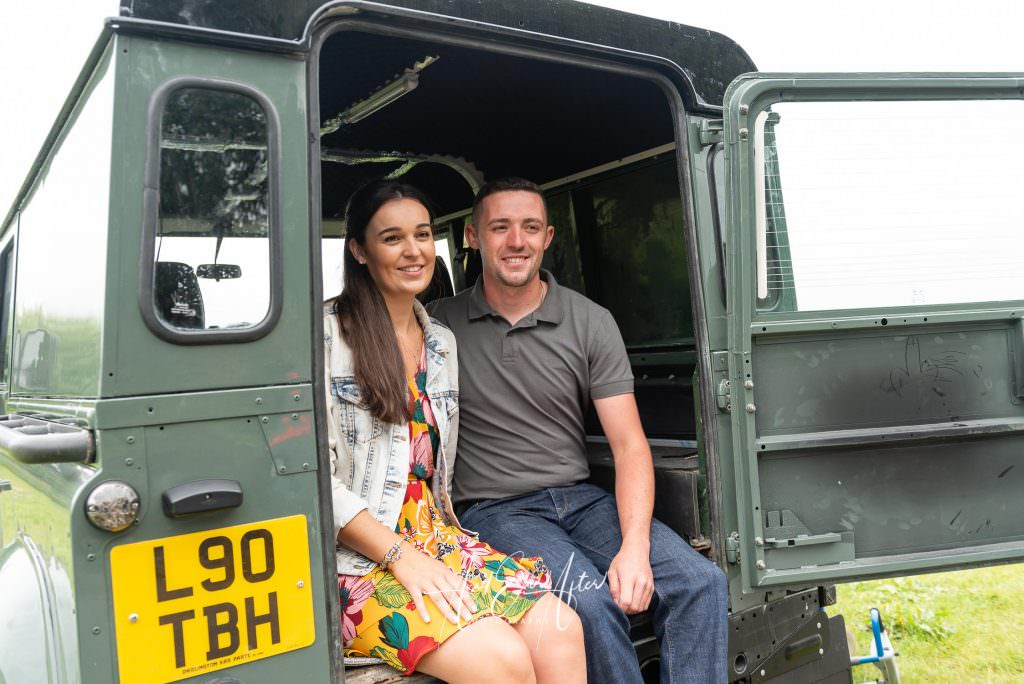 pre wedding photo shoot with bride and groom sitting in back of their Land Rover