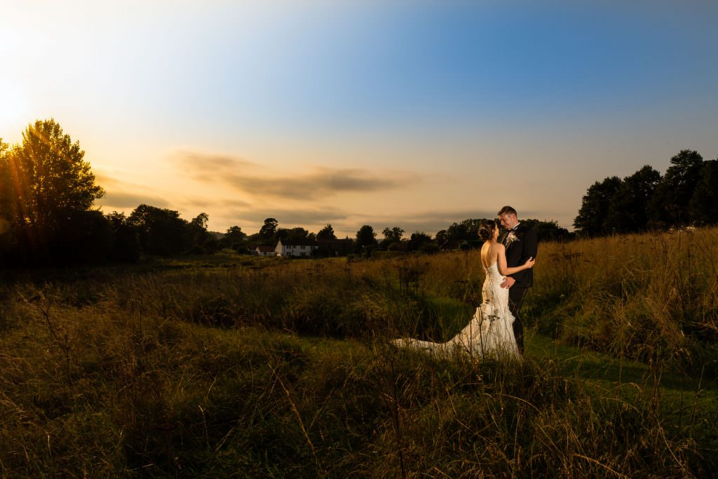 bride and groom holding each other in field at sunset