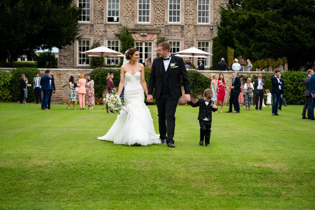 bride and groom walking with their son at Headlam Hall